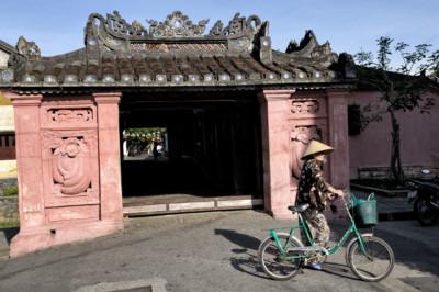 Femme à vélo devant le pont pagode japonais à Hoi An, Vietnam