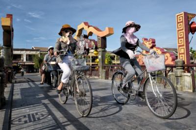 Femmes avec le visage couvert sur un pont de Hoi An, Vietnam