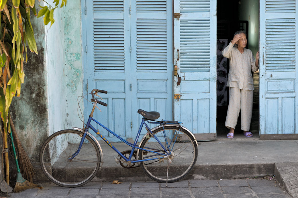 Vielle femme devant sa porte de volets bleus à Hoi An, Vietnam