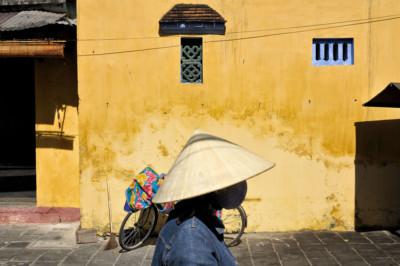 Passante devant un mur jaune à Hoi An, Vietnam