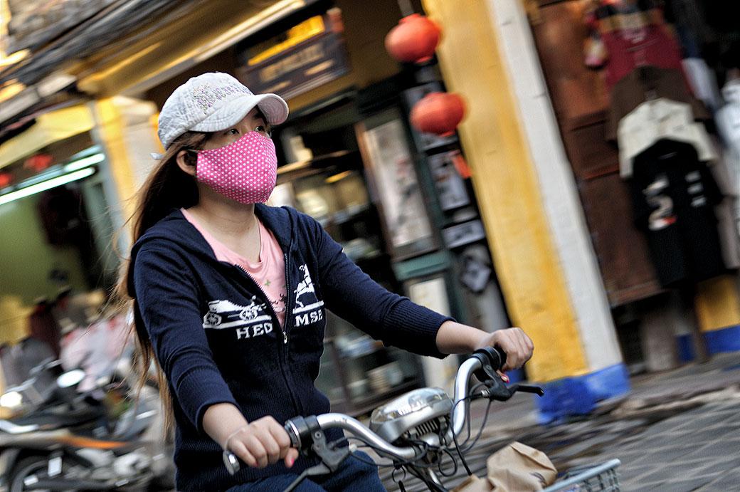 Femme à vélo portant un masque à Hoi An, Vietnam