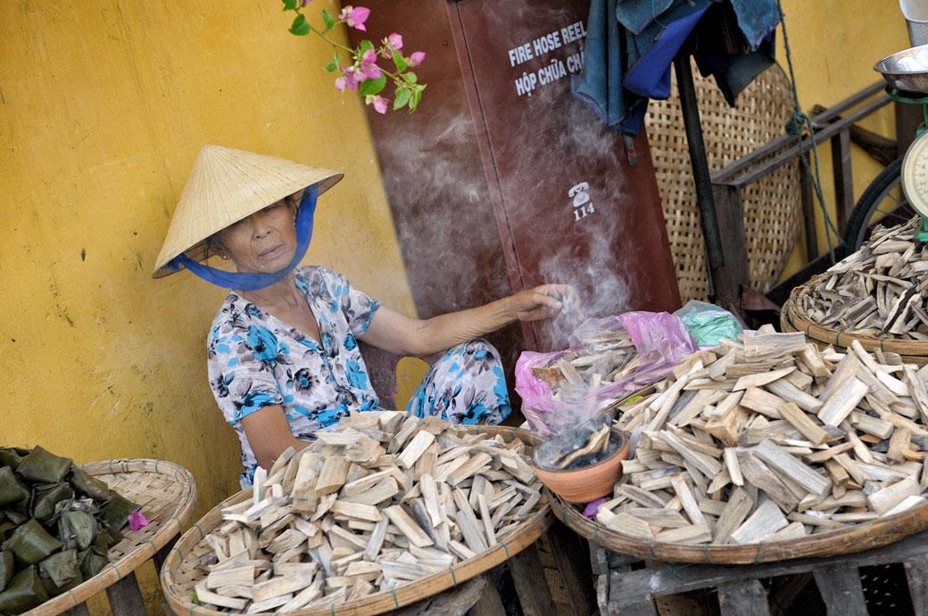Vendeuse de petits bois au marché de Hoi An, Vietnam