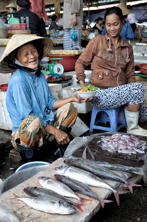 Vendeuse de poissons heureuse au marché de Hoi An, Vietnam