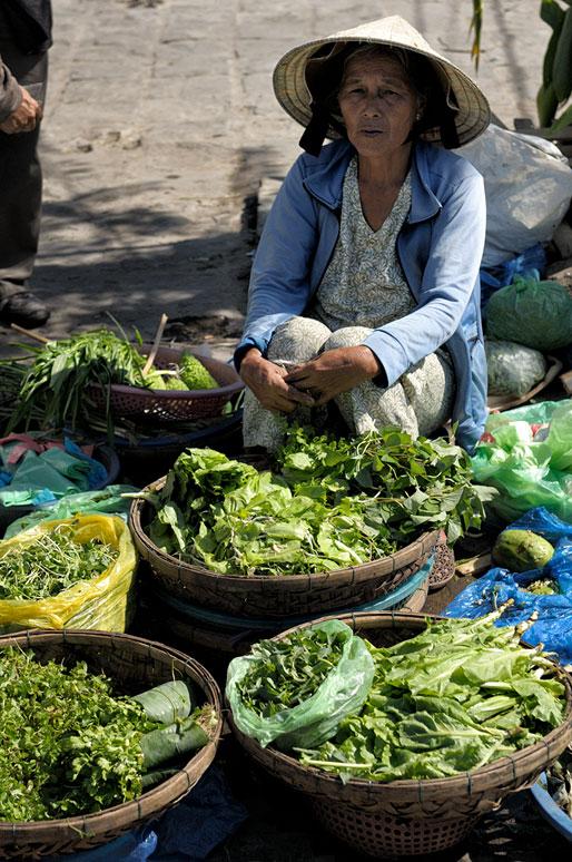 Vendeuse de légumes verts au marché de Hoi An, Vietnam