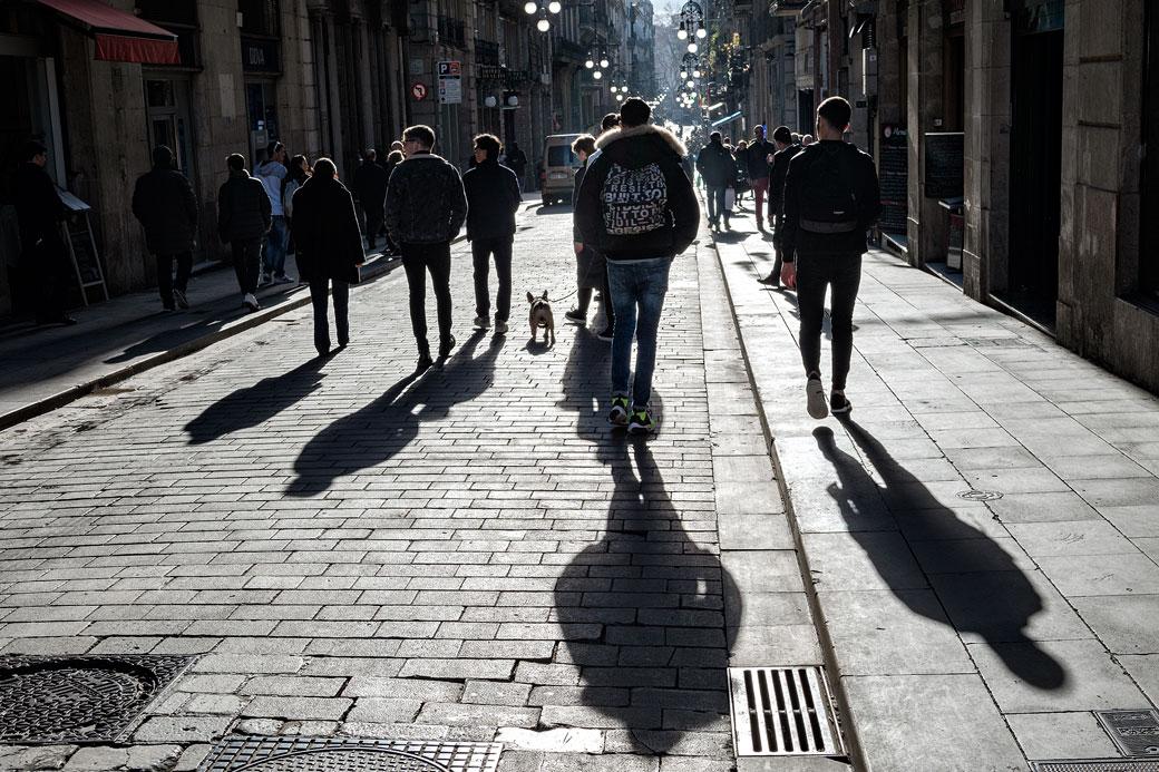 Ombres et passants dans une rue de Barcelone