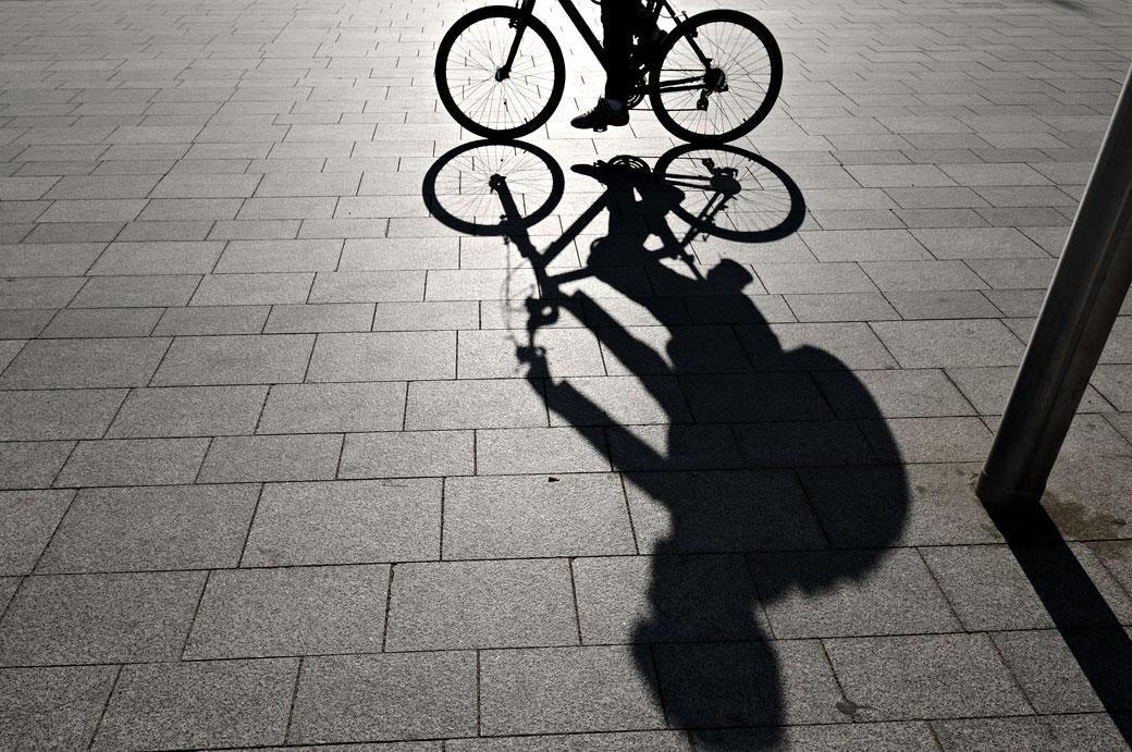 Cycliste et son ombre sur une place de Barcelone