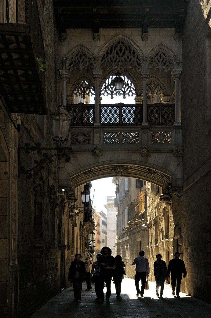 Passants sous le Pont del Bisbe à Barcelone