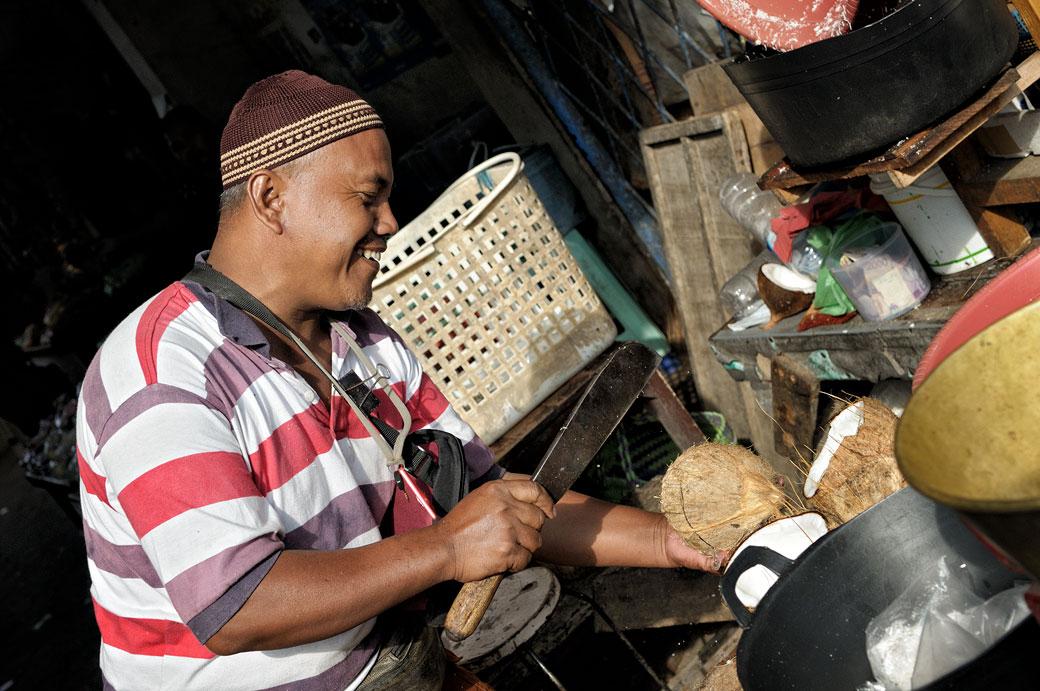 Homme qui casse une noix de coco au marché de Borobudur, Indonésie