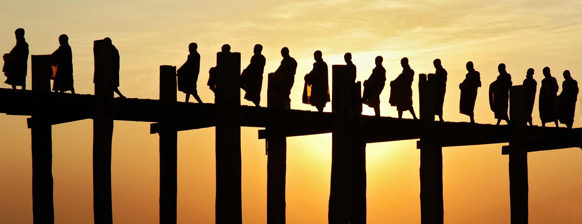 Des moines défilent sur le pont U Bein au coucher du soleil, Birmanie