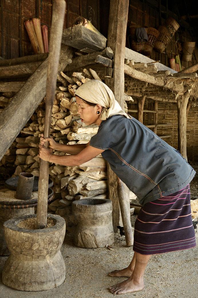 Femme Loi qui bat les graines de la récolte à Wun Nyat, Birmanie