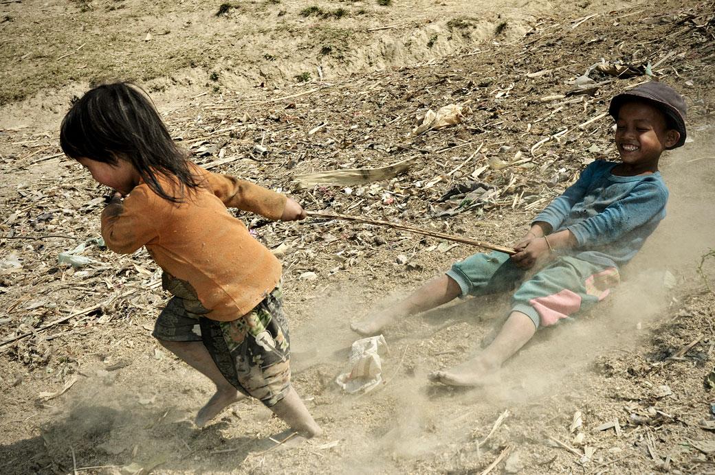 Jeu d'enfants dans la poussière à Wun Nyat, Birmanie