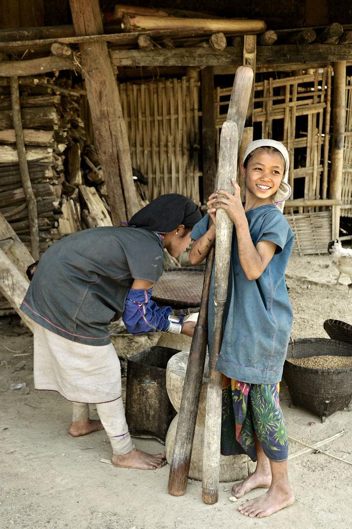 Fillettes Loi qui battent les graines de la récolte, Birmanie