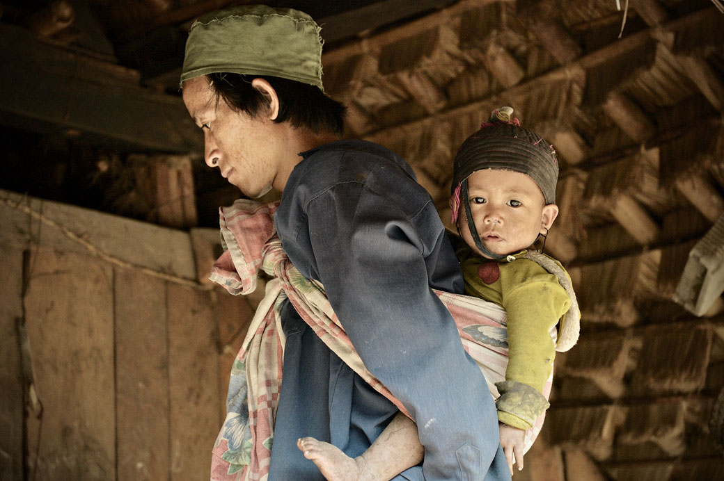 Homme Loi avec son bébé dans une maison à Wun Nyat, Birmanie