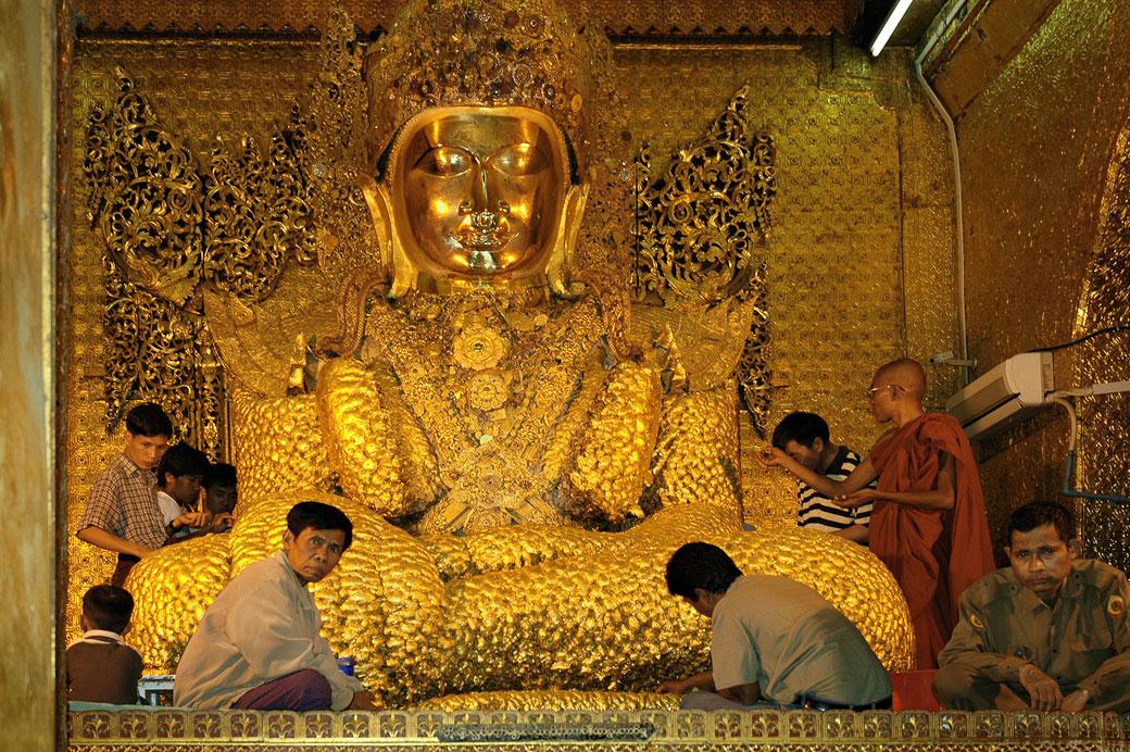 Fidèles au pied du bouddha en or de Mahamuni à Mandalay, Birmanie