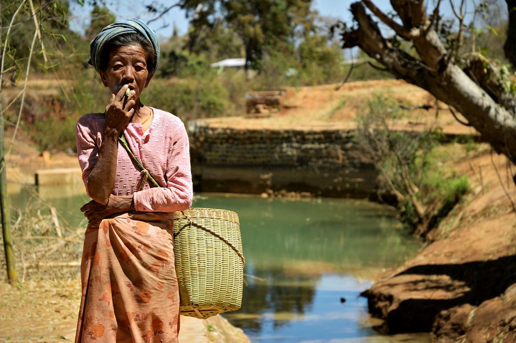 Femme birmane qui fume un cheerot debout, Birmanie
