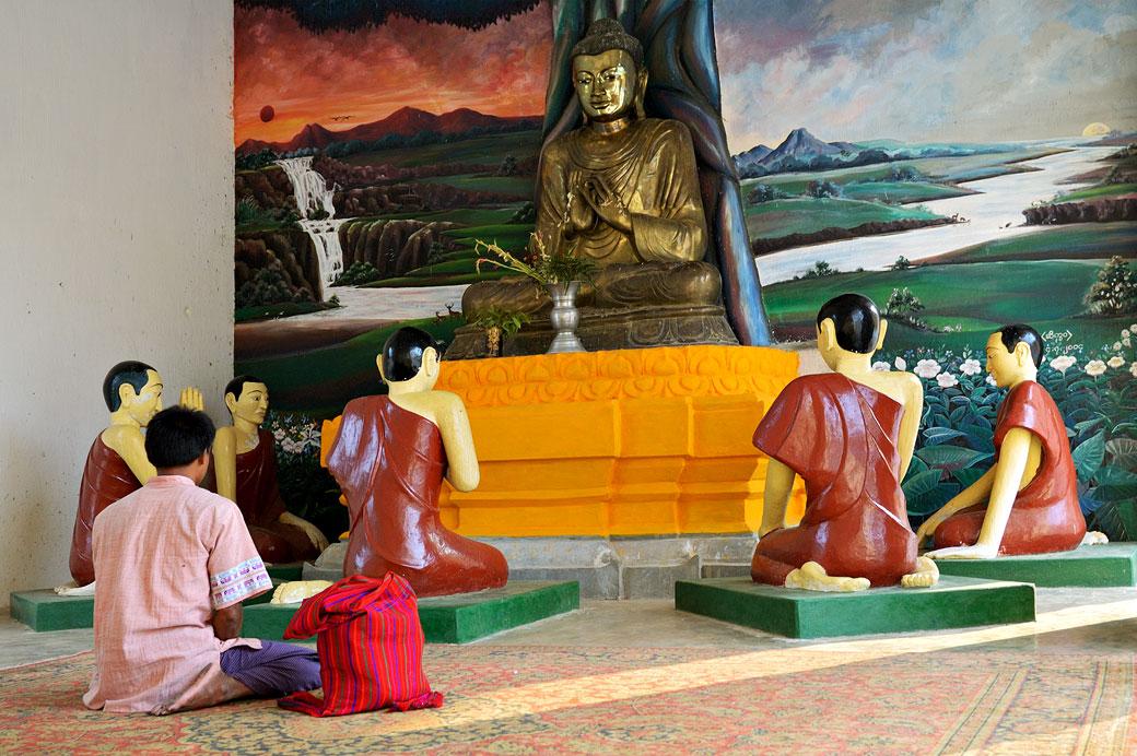 Homme qui médite près d'une statue de bouddha et ses disciples, Birmanie