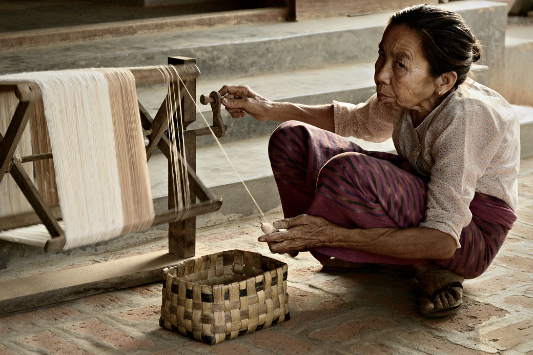 Vieille femme accroupie avec son rouet, Birmanie