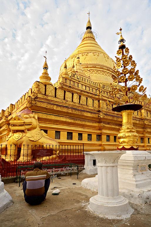 Un homme médite devant la pagode Shwezigon de Bagan, Birmanie
