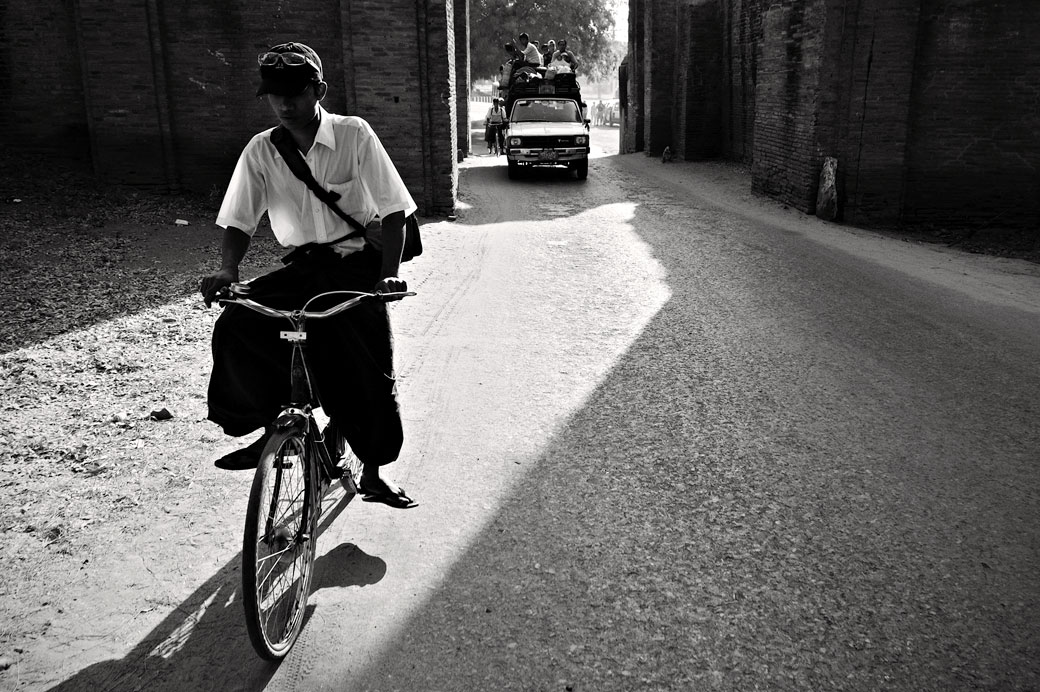 Un cycliste et un minibus bien chargé à Bagan, Birmanie