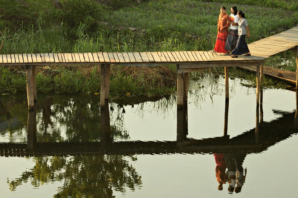 Réflexion de trois copines sur une passerelle sur le lac Inle