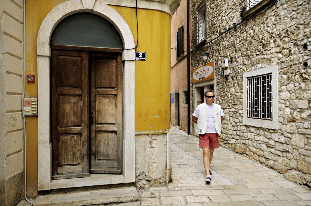 Porte et touriste dans une ruelle de Poreč, Croatie