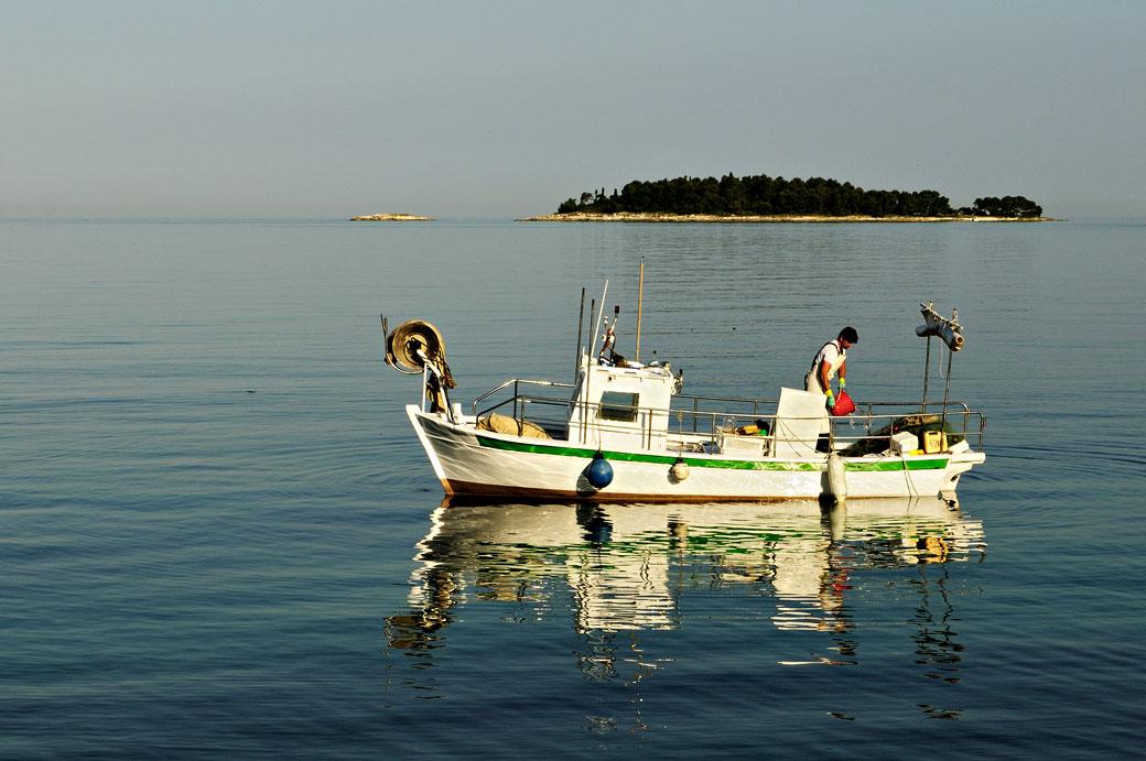 Pêcheur sur un bateau blanc au large de Rovinj, Croatie