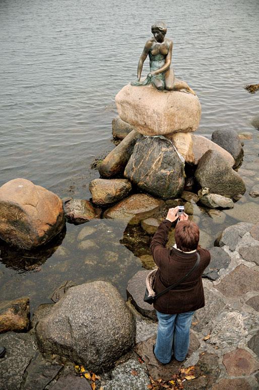 Une femme photographie la statue de la Petite Sirène à Copenhague