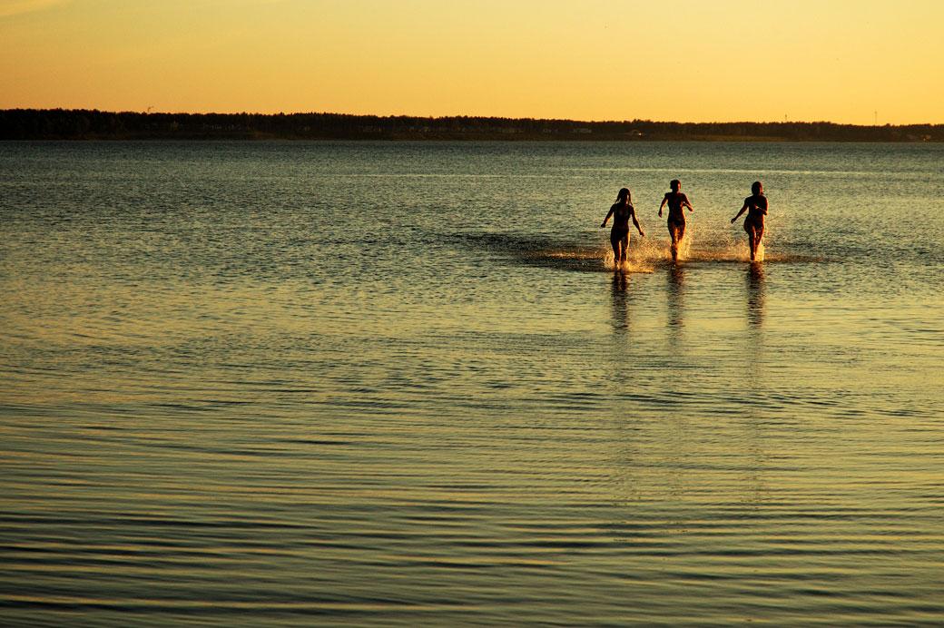 Jeunes femmes qui courent dans la mer Baltique à la plage de Stroomi