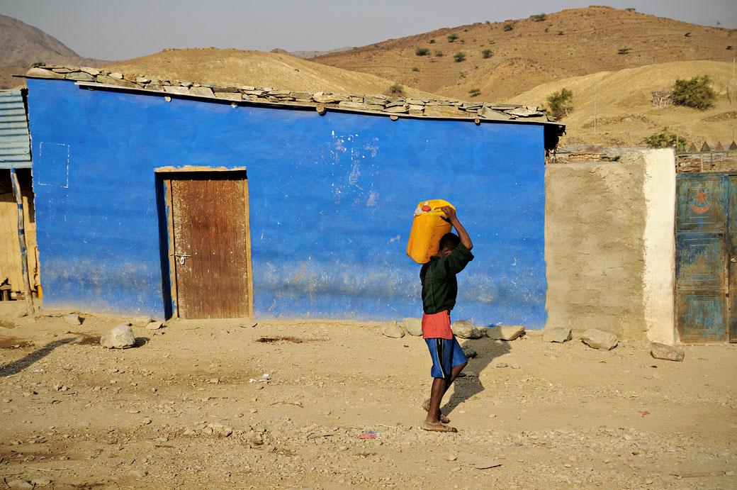 Passant devant une maison bleu dans une rue de Berahle, Ethiopie