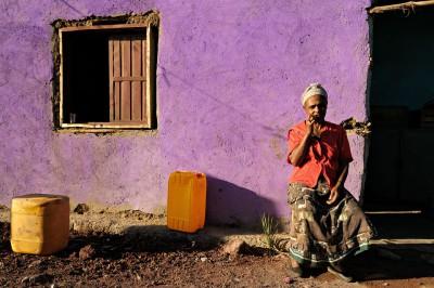 Femme devant sa maison au mur violet, Ethiopie