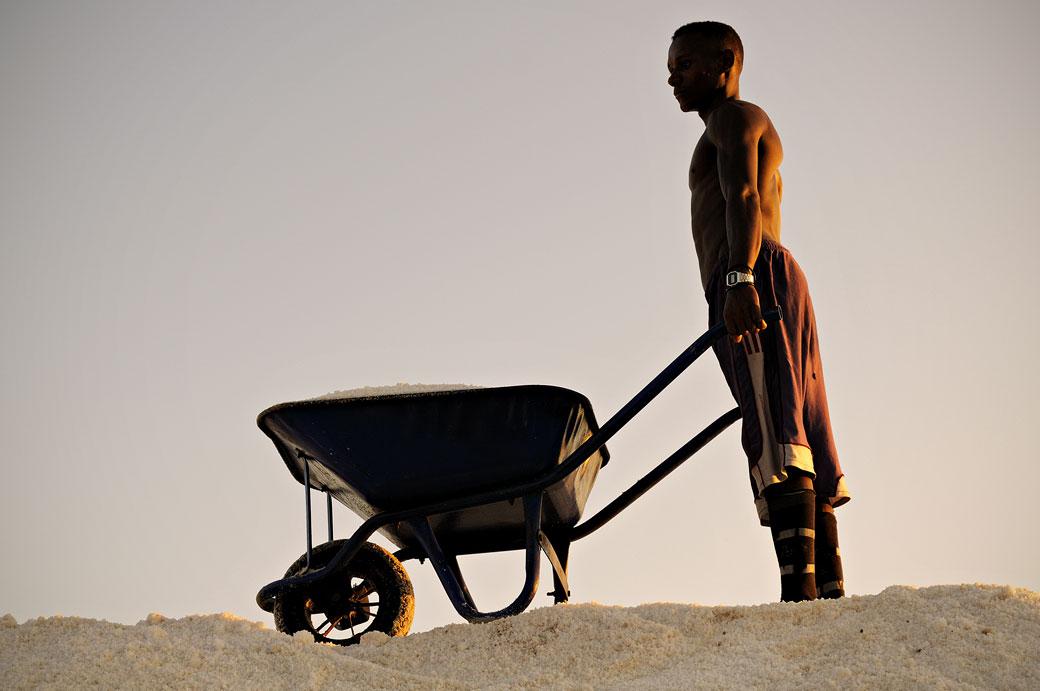 Homme avec sa brouette sur un tas de sel à Afdera