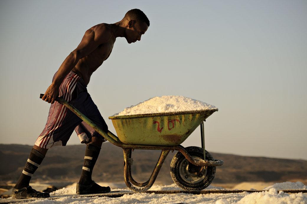 Homme musclé avec une brouette pleine de sel dans les salines d'Afdera