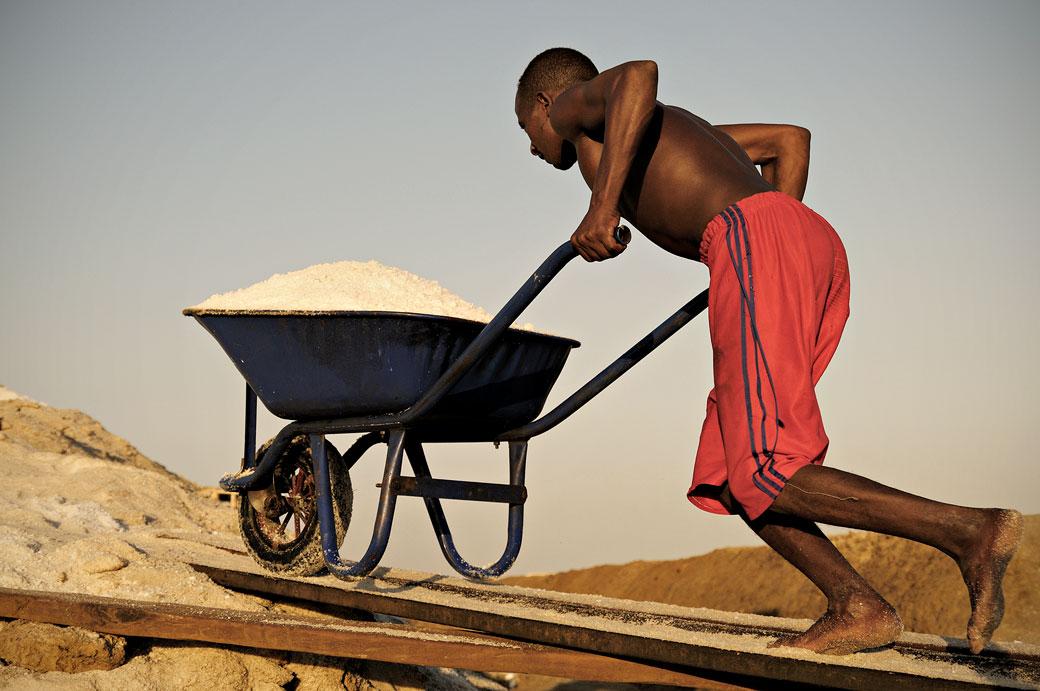 Homme avec sa brouette remplie de sel dans les salines d'Afdera