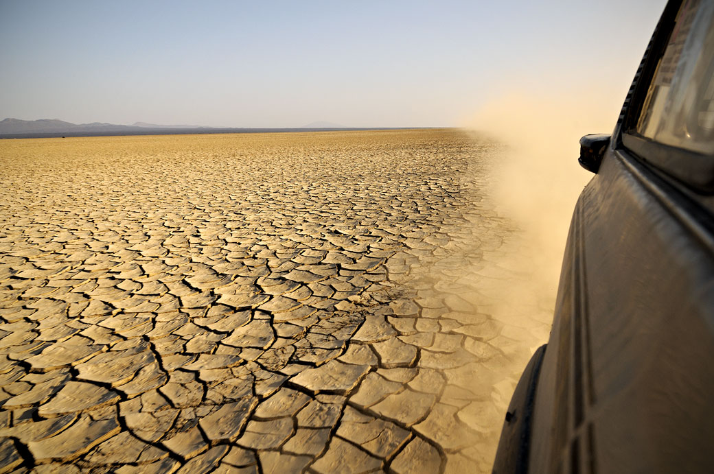 Voiture qui soulève de la poussière dans le désert du Danakil, Ethiopie