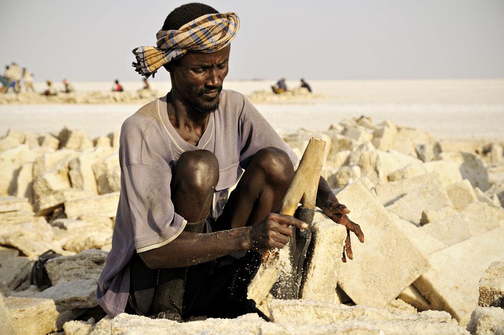 Un homme taille des plaques de sel sur le lac Assale, Ethiopie