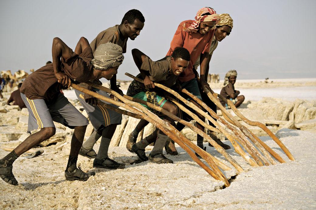 Hommes avec des pieux pour soulever un bloc de sel du lac Assale