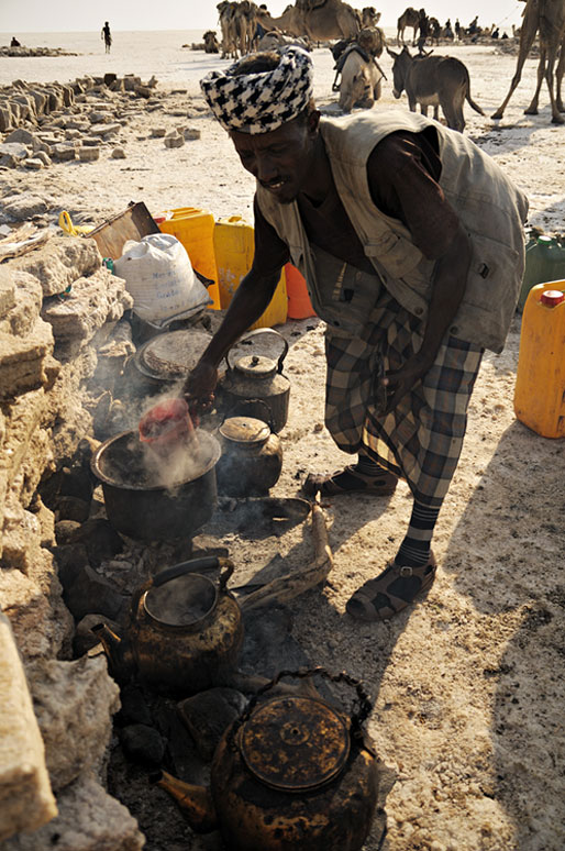 Un homme prépare le thé pour le travailleurs sur le lac Assale