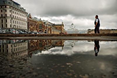 Reflet d'un passant et de la cathédrale dans une flaque d'eau, Helsinki