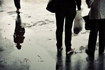 Reflet d'une passante dans une flaque d'eau à Helsinki, Finlande