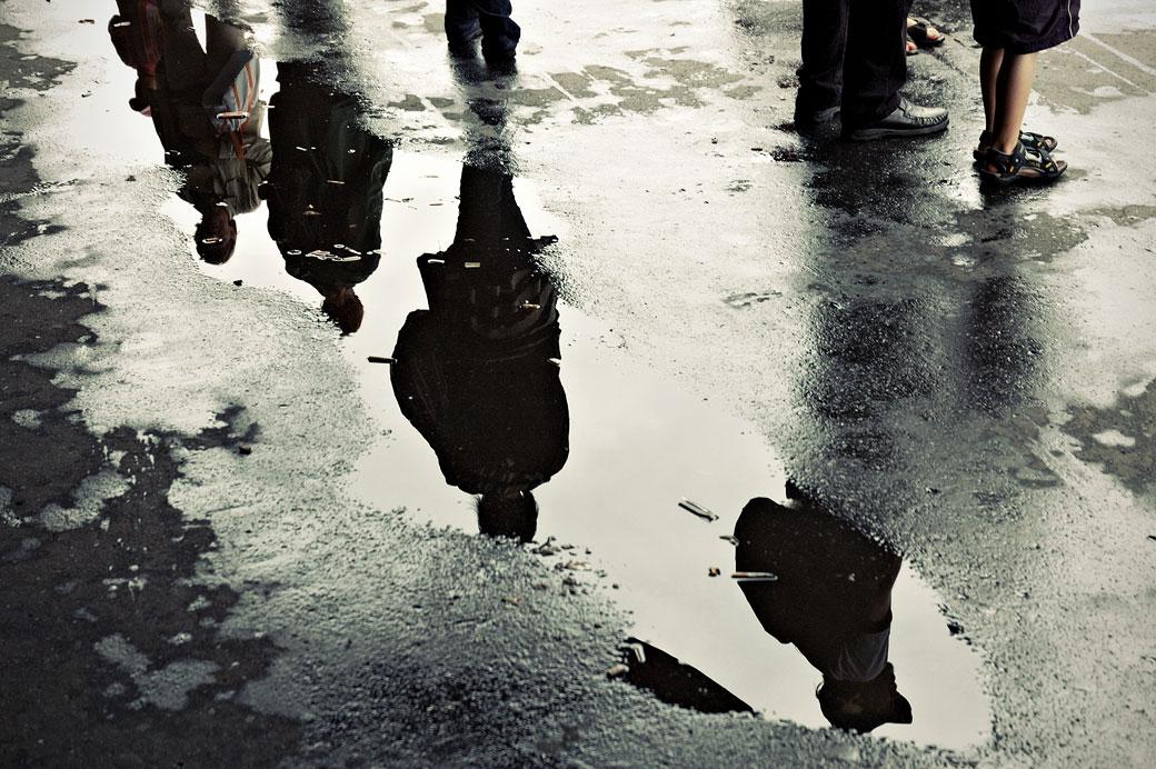 Reflet de passants dans une flaque d'eau à Helsinki, Finlande