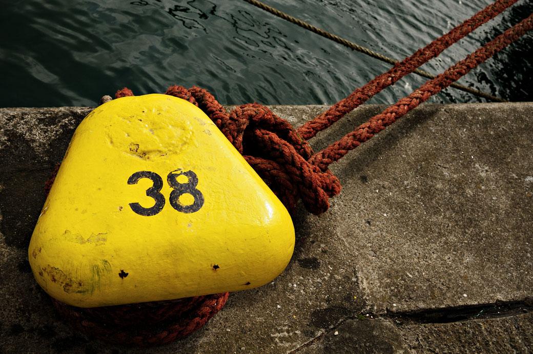 Corde accrochée à un bollard jaune dans le port de Howth