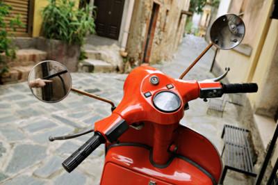 Scooter rouge dans une rue de Castelmola en Sicile, Italie