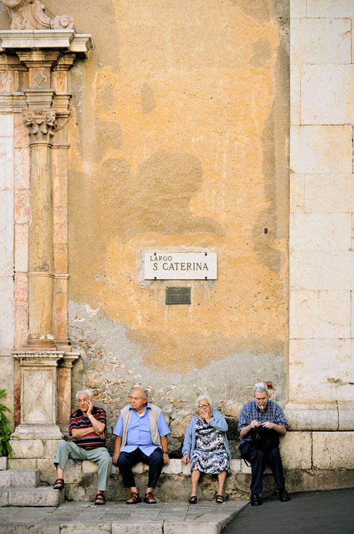 Personnes assises devant l'église Sainte Catherine à Taormine en Sicile