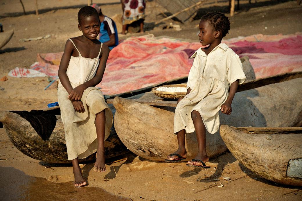 Jeunes filles et pirogues sur la plage à Cape Maclear, Malawi