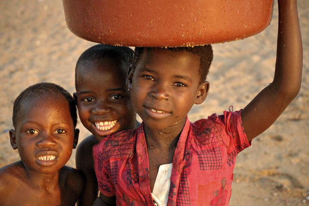 Enfants tout sourire avec une bassine d'eau à Cape Maclear, Malawi