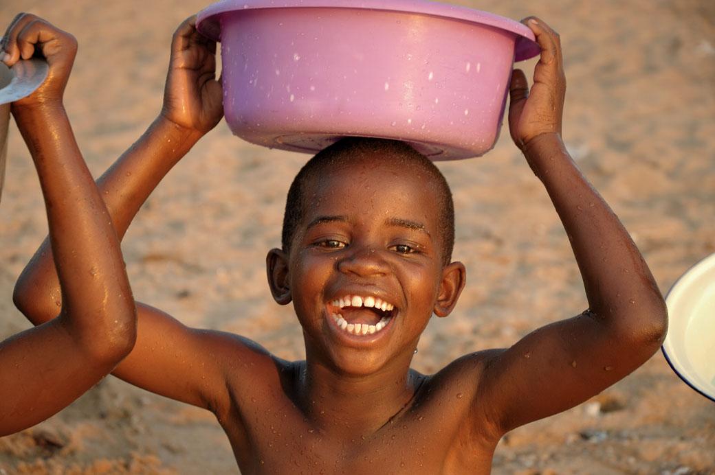 Enfant souriant avec une bassine sur la tête, Malawi
