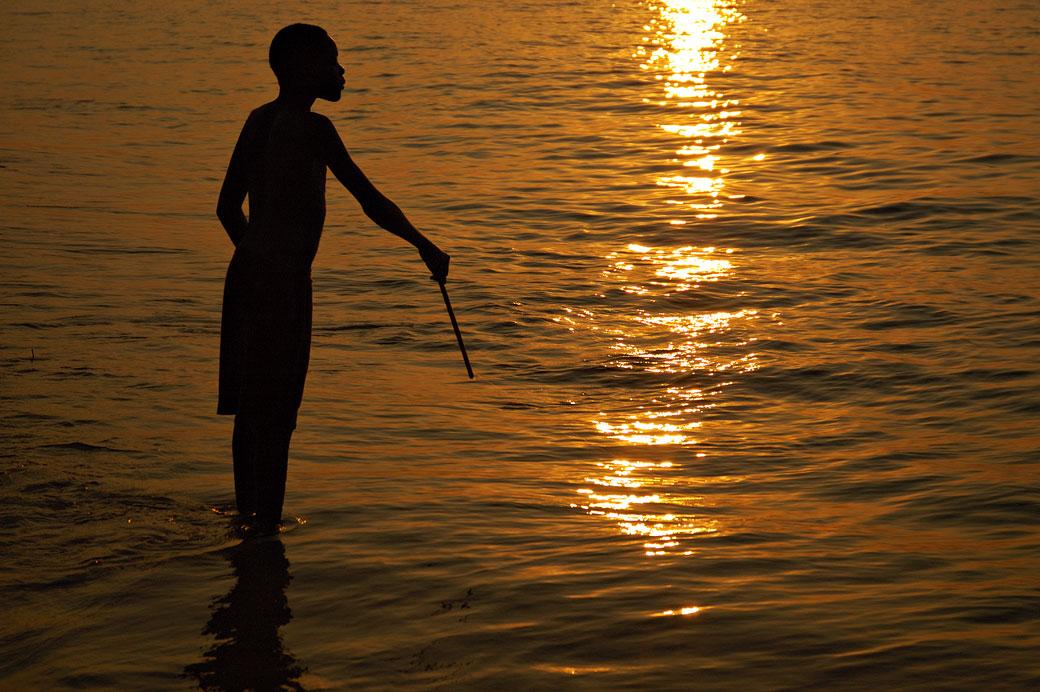 Silhouette d'un pêcheur au coucher du soleil au lac Malawi