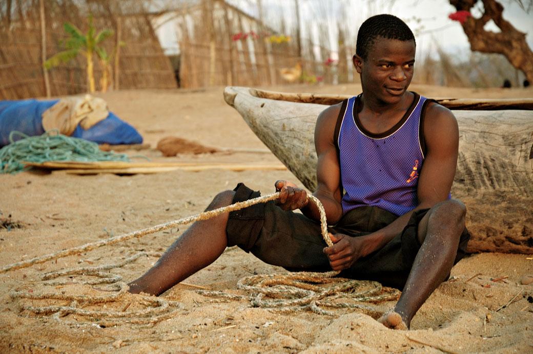 Jeune homme avec une corde sur la plage à Cape Maclear, Malawi