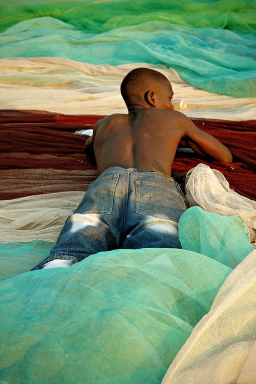 Pêcheur couché sur un filet de pêche coloré à Cape Maclear, Malawi