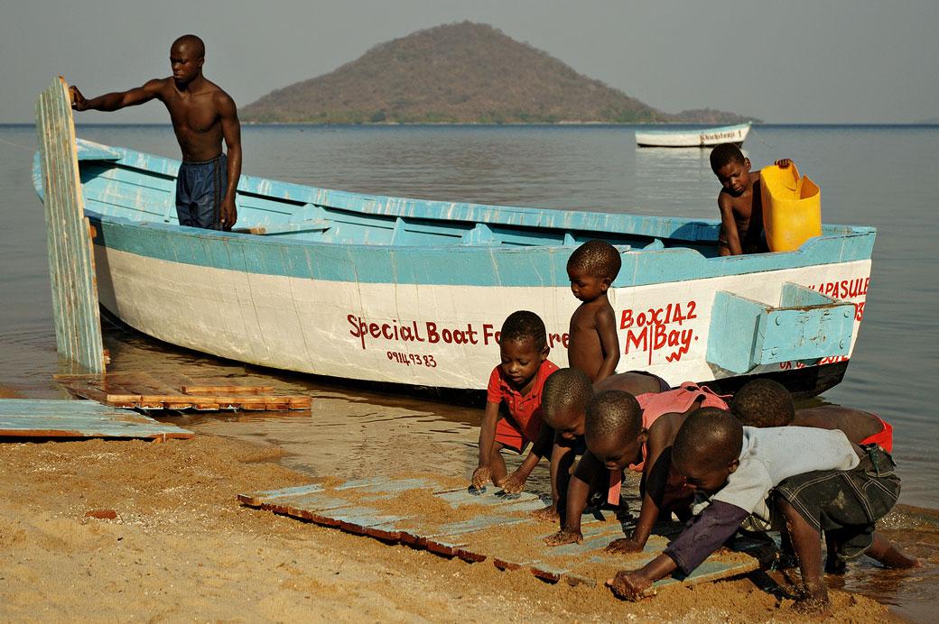 Homme qui nettoie son bateau avec des enfants à Cape Maclear